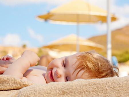 Happy baby sunbathing on the beach sunbed. Summer holidays concept. Stockfoto