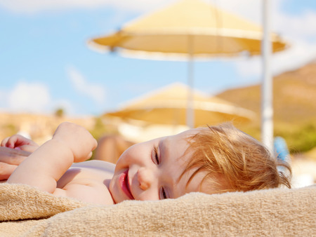 Happy baby sunbathing on the beach sunbed. Summer holidays concept. Stock Photo