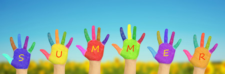kids painted hands: Kids painted hands forming word summer.on a background of field of sunflowers and blue sky in sunny day. Summer holidays concept. Stock Photo