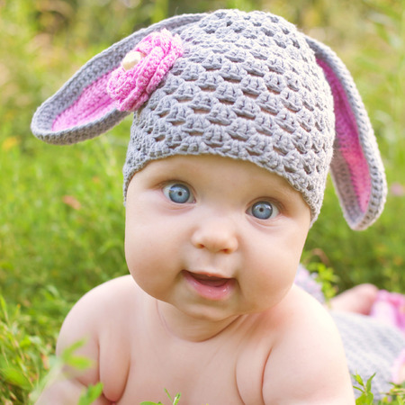 Baby in the hat like easter bunny or lamb of green grass, closeup face.