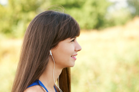 down beat: Pretty woman listening to music, face closeup. Resting in the park. Stock Photo