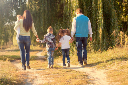 Family Ties concept. Big happy family walking on the path in the park. Rear view.