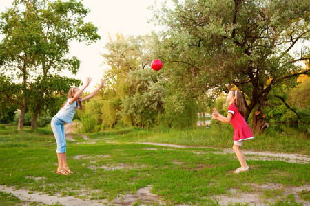 suburban neighborhood: Kids playing in a suburban neighborhood. Two sisters or girlfriends throwing the ball to each other.