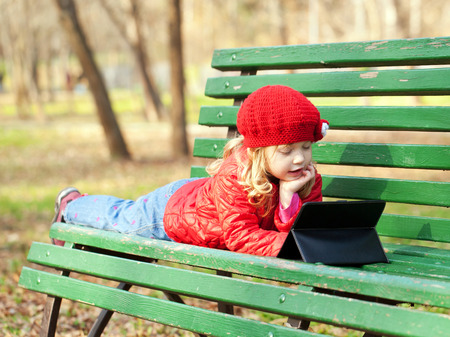 Kid with technology outdoors in the park photo