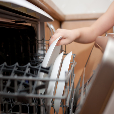 domestic scene: Childs hand putting a plate in the dishwasher. Kids housework.
