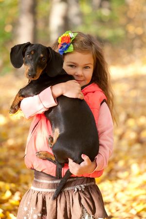 puppy love: Ni�o que abraza el perrito perro salchicha. Amor a los animales concepto Foto de archivo
