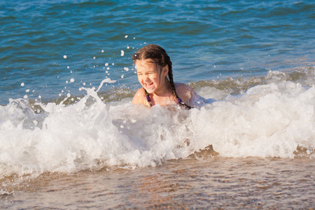 Happy kid playing playing on beach in the sea waves photo