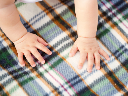 Toddler crawling on a picnic blanket. Baby hands close-up. Stock Photo