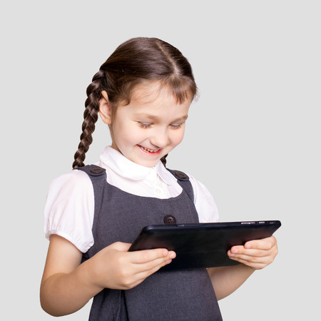 learning: Little student girl using tablet pc or e-book. Digital learning. Isolated on a gray background.
