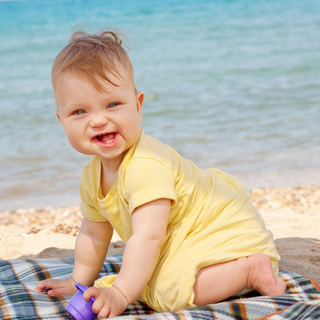 baby tooth: Smiling baby playing on the beach