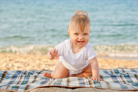 baby crawling: Happy baby crawling on the beach. Summer vacation.