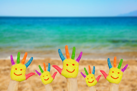 face of baby: Smiley on hands against beach sand sea and sky background. Summer vacation concept with copy space