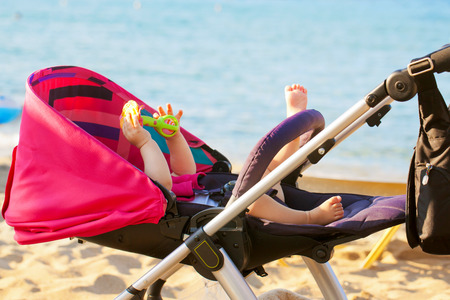 Baby lying in a stroller on the beach against the sea background. Summer vacation