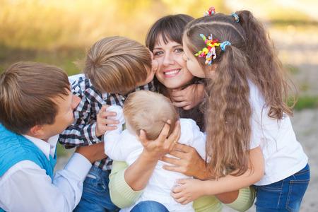 hugs: Large family hugging and having fun outdoors. Stock Photo