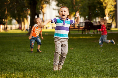Group of kids playing in an urban neighborhood with bubbles. Stock Photo