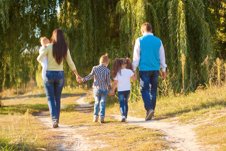Big happyfamily walking in a city park. Rear view