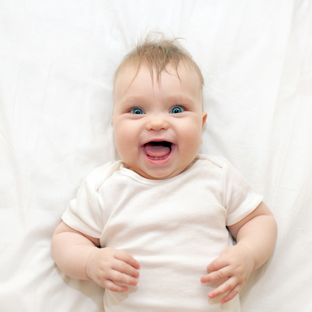 Smiling surprised baby lying on a white bed. Good morning! Standard-Bild