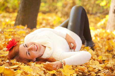 redhaired: Red-haired young woman lying among red leaves in autumn forest. Outdoor portrait