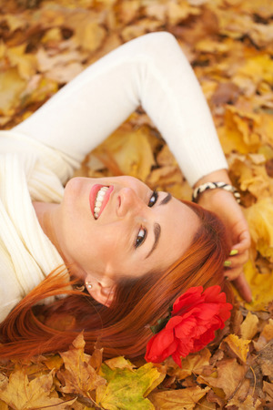 Red-haired young woman lying among red leaves in autumn forest. Outdoor portrait photo