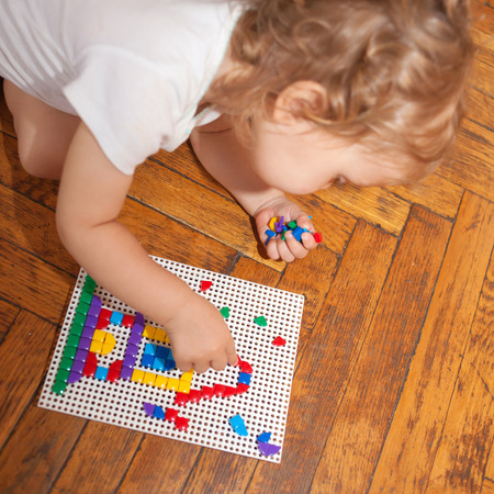 assiduous: Baby playing and creating a house of mosaics on the floor. Selective focus on the mosaic.
