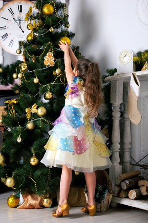 woman hanging toy: The girl in a beautiful dress decorating the Christmas tree. Waiting for the New Year and Christmas. Stock Photo
