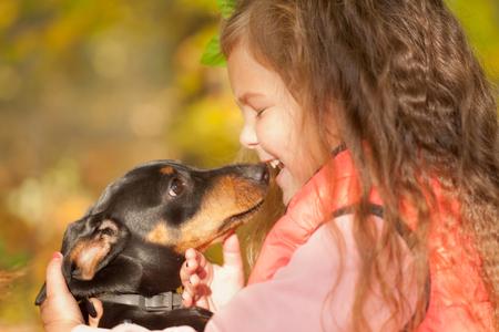 puppy love: Ni�o que besa el perrito perro salchicha. Amor a los animales concepto Foto de archivo
