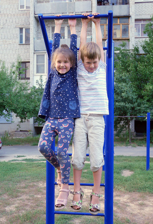 boy gymnast: Boy and girl playing in the yard on the playground. Children are hanging on the bar.