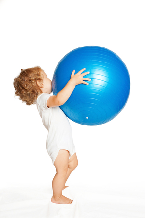 exhilarated: Baby playing with a large fitness ball. Isolated on white background
