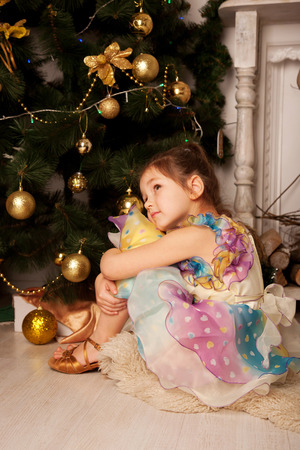 miracle tree: Child waiting for the miracle and gifts near the Christmas tree on Christmas Eve