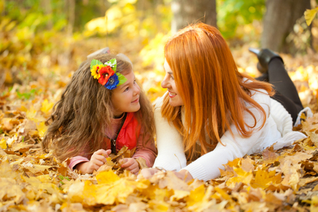 Mother and little daughter having fun and talking in the autumn park. photo
