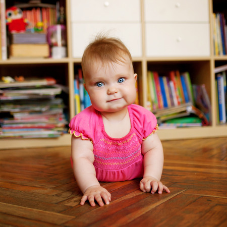 baby crawling: Baby crawling on the wooden floor in the nursery, against the bookcase.