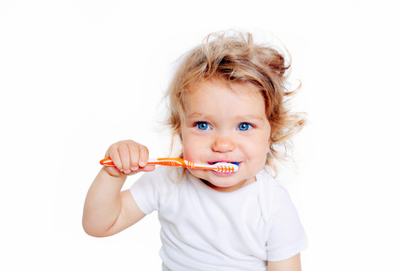 healthy smile: Curly baby toddler brushing teeth. Isolated on white background. Stock Photo