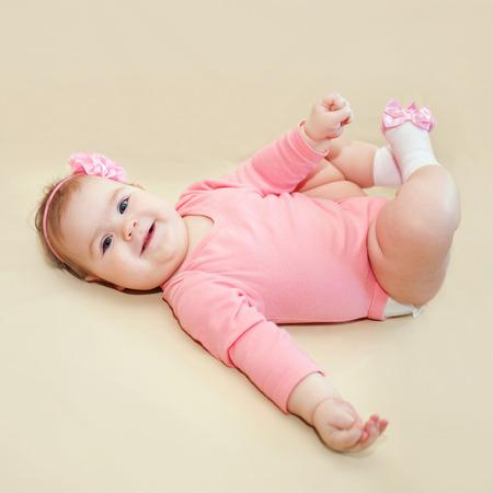 Bebé feliz jugando con sus pies sobre un fondo de color beige.