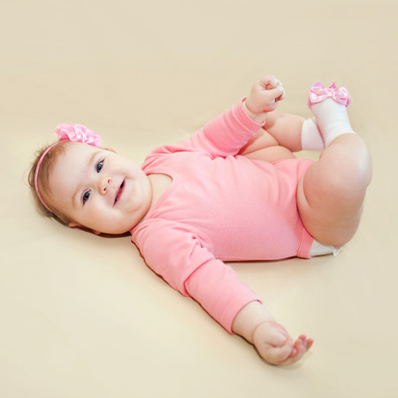 girl socks: Happy baby girl playing with her feet on a beige background. Stock Photo