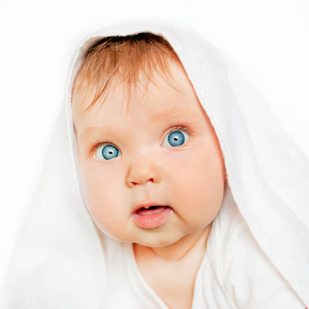 surprised baby: Surprised baby under the white towel after bath on white background. Stock Photo