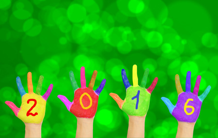0 1 year: Kids colorful hands forming number 2016 against New Year blurred bokeh green background. Stock Photo