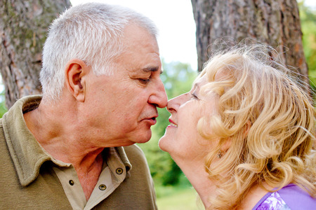romance sex: Two happy seniors kissing and having fun together.