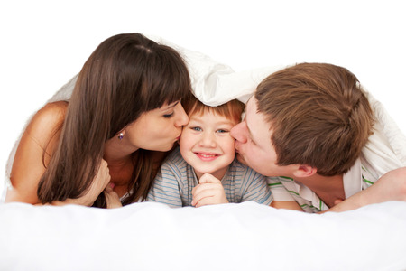kiss: Happy parents kissing child in bed covered with a blanket. Good morning! Isolated on white background.