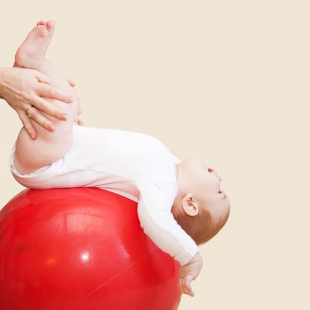 massage enfant: Remise en forme de bébé. Mère faire de massage et salle de gym exercices avec son enfant. Isolé sur le fond beige