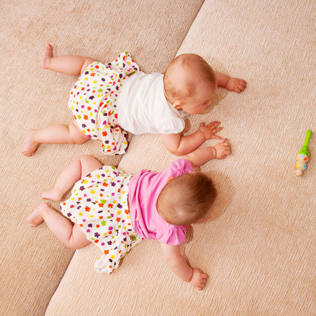 overtake: Two baby twins crawling together on the sofa