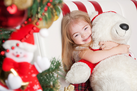 syndrome: Lovely little girl hugging a teddy bear. Winter holidays.