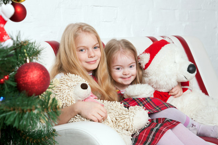 christmas time: Two little sisters with teddy bears under the Christmas tree. Winter holidays. Stock Photo
