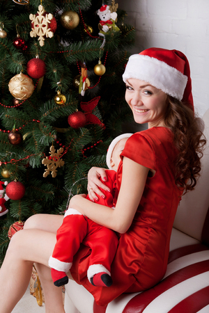 nude baby: Mother breast feeding baby. Family dressed in Santa`s costumes. Winter holidays. Christmas, new year and people concept.