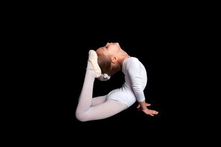 zapatillas ballet: Pequeña bailarina haciendo ejercicios de gimnasia de estiramiento. Aislado en un fondo negro.