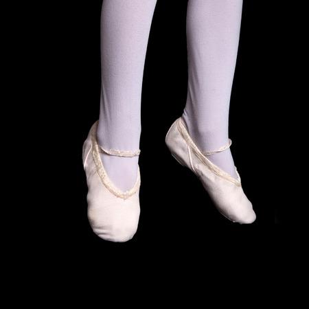 d601054ab Las piernas y los pies de poca 6 de la bailarina que en la posición de  punta. Aislado en un fondo negro.
