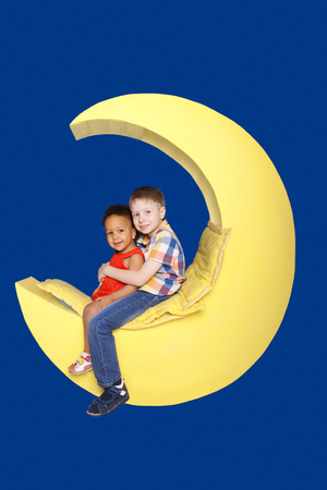 new generation: Children - white boy and black girl sitting on the moon. New generation dream and goal concept. Isolated on blue background.