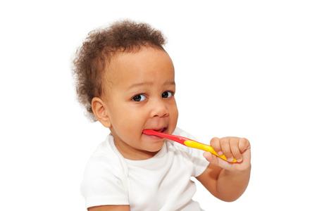 teething: Black baby toddler brushing teeth. Isolated on white background.