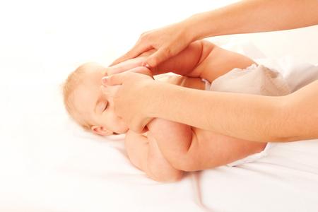 baby massage: Le massage de b�b�. Pieds de b�b� touchant son front. Isol� sur fond blanc Banque d'images