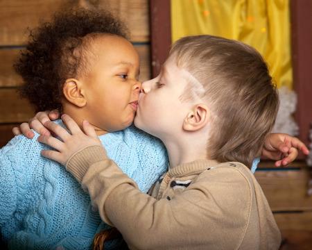 Czarny Dziewczyna całuje białego chłopca. Dzieci uwielbiają.