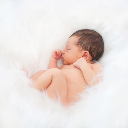 nude baby: Sleeping newborn baby in the white fur. Birth and a new life concept.